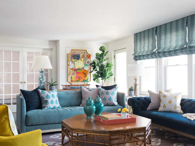family room with blue velvet sofa, yellow chair, and roman shades