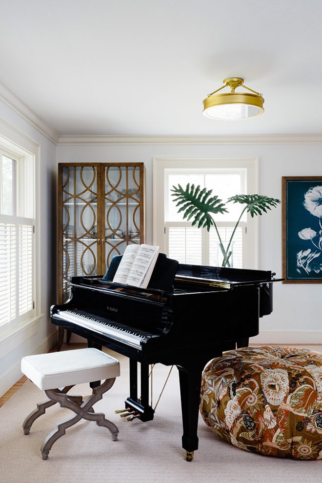 modern farmhouse living room with baby grand piano and upholstered ottoman