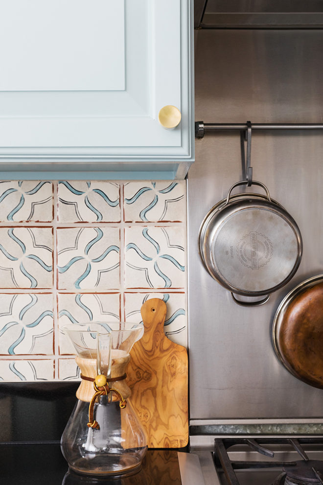 blue kitchen cabinets with brass pulls and terracotta tile